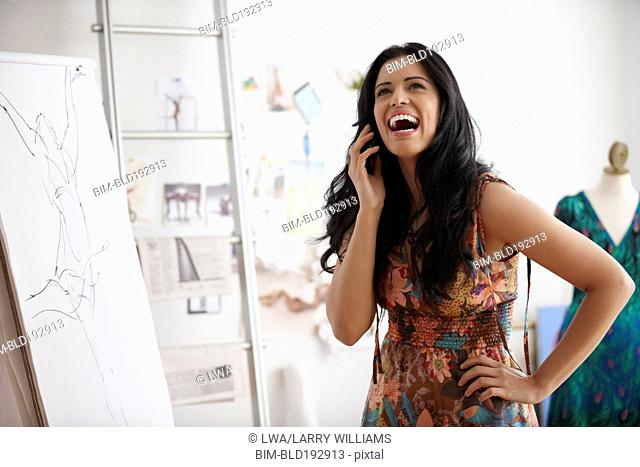 Mixed race woman talking on cell phone in design studio