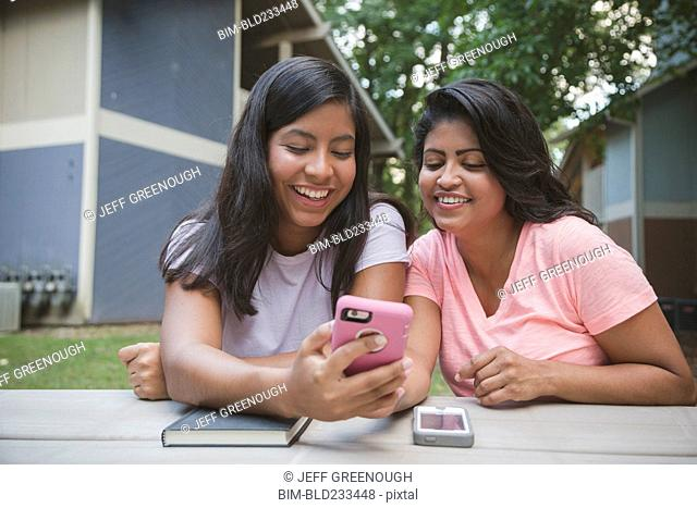 Hispanic mother and daughter texting on cell phone near apartments