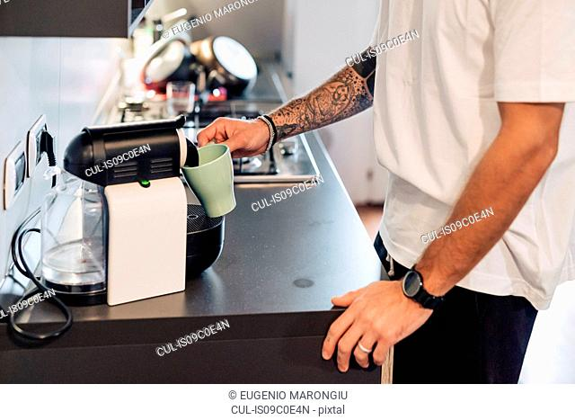 Mid adult man pouring coffee from coffee machine on kitchen counter, mid section