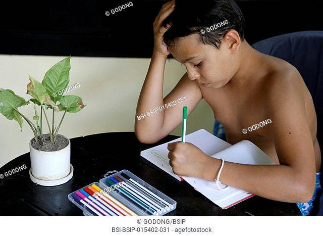 10-year-old European boy writing a vacation diary. Cambodia