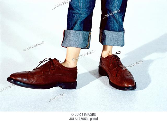 View of young child's feet in businessman's shoes