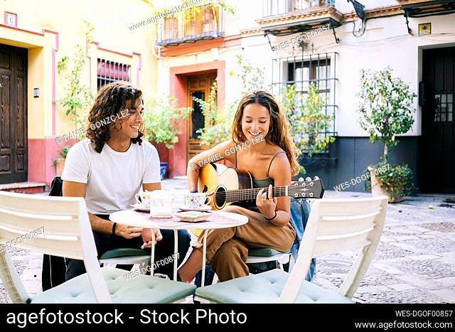 Smiling young man looking at girlfriend playing guitar while sitting at sidewalk cafe, Santa Cruz, Seville, Spain