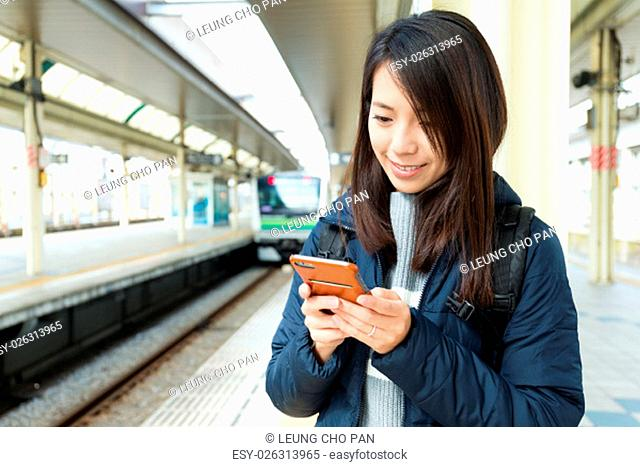Woman texting message on cellphone in train station