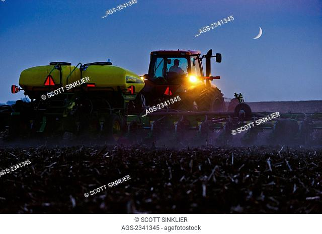 Agriculture - A farmer plants a soybean crop at night with a crescent moon above the field. Corn stubble is left over from the previous year's corn harvest /...