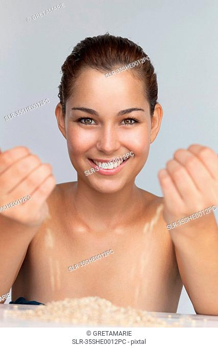 Smiling woman playing with grains