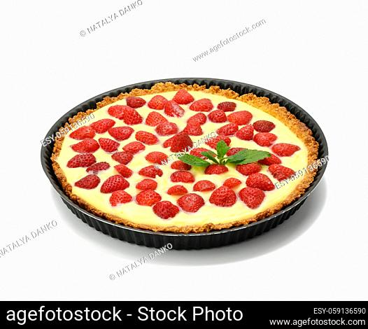 baked round tart with strawberries and tender milk cream isolated on white background, top view