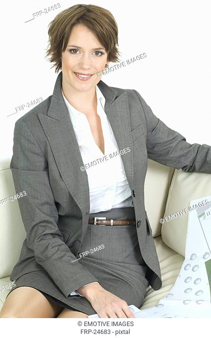 Young woman in business dress working on sofa
