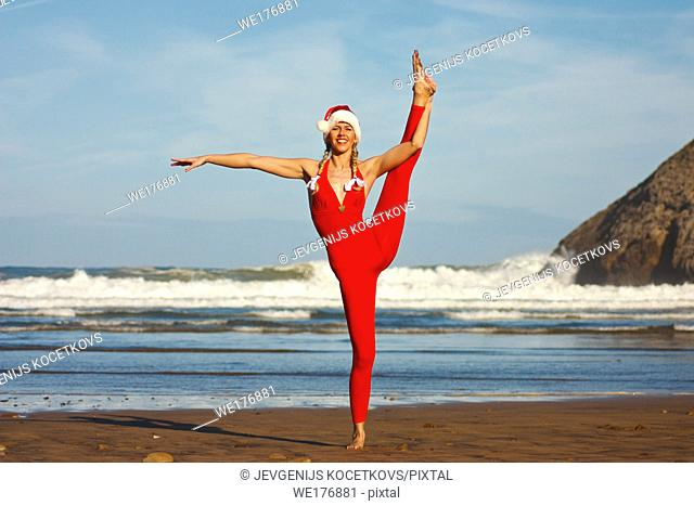 Woman in Christmas costume doing standing splits on the beach