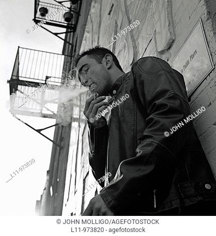 Man in alley, wearing a leather jacket and smoking a cigarette
