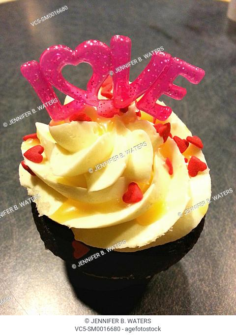 A cupcake topped with a LOVE decoration