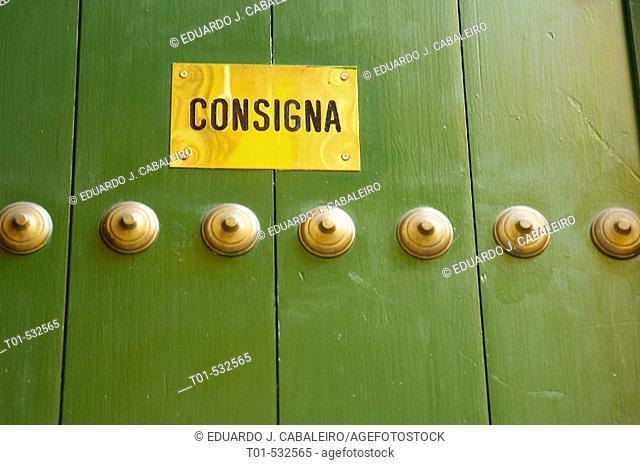 green door with golden poster slogan of left luggage office