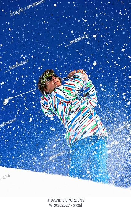 Golfer watches after driving ball on snowy alpine course