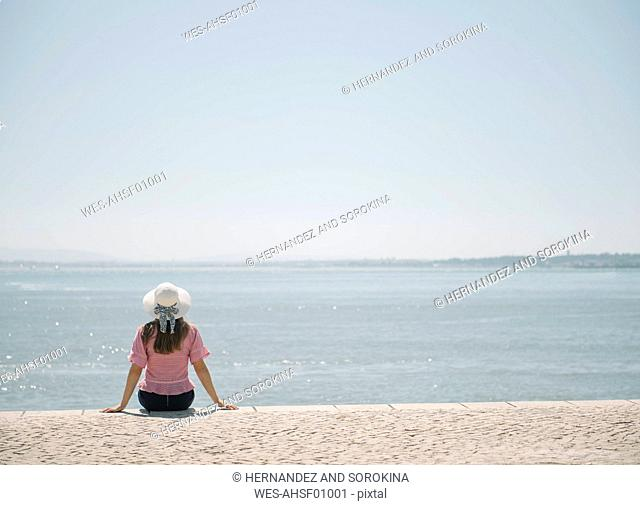 Rear view of woman sitting at the coast, Lisbon, Portugal