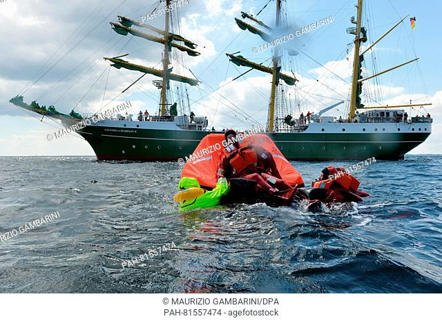 Emergency physicians wearing immersion suits mount a life raft next to the training sailing ship 'Alexander von Humboldt II' during a drill off Fehmarn, Germany