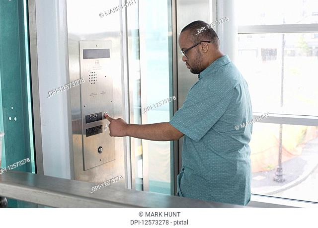 African American man who has Down Syndrome using an elevator