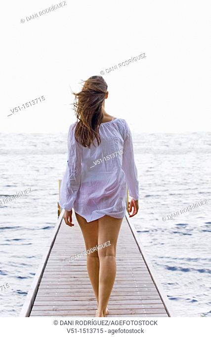 Young woman walking untill the end of a pier