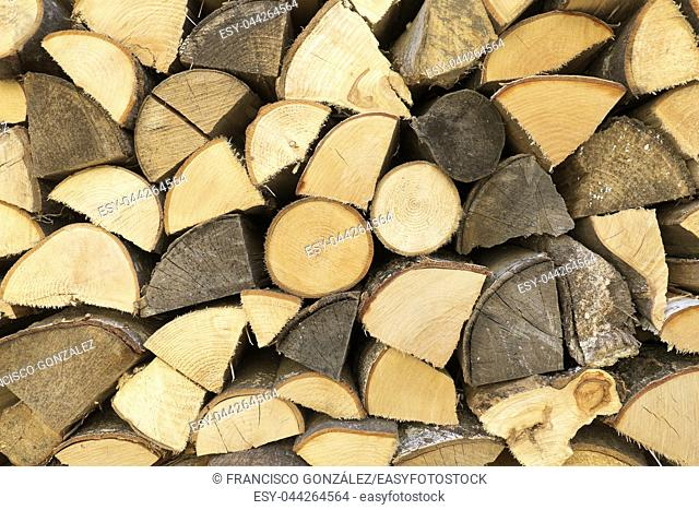 Wooden logs arranged in a wood of a Swiss village. Horizontal shot with natural light