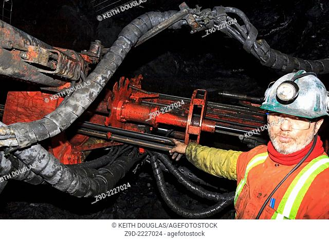 Underground miner next to mining drill rig called a 'Jumbo' working at rock face, Eskay Creek mine, Iskut, British Columbia