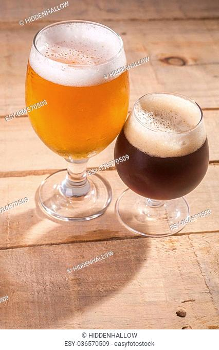 Small glass of dark beer and larger glass of light beer on a wooden table
