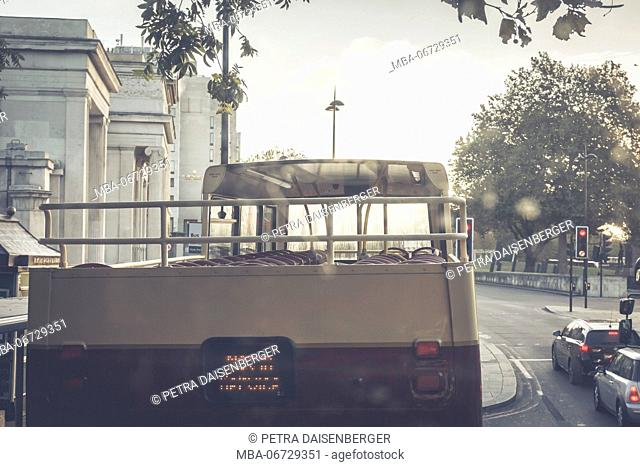 An open double decker bus on his journey through London early in the morning