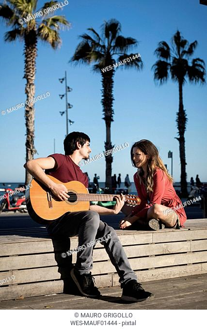Spain, Barcelona, smiling couple with a guitar sitting on a bench at seaside promenade