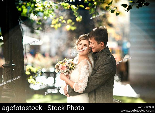 Groom hugs bride against the background of the old city center