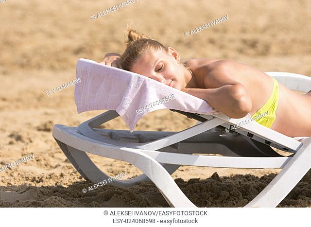 Young girl is lying on a deck chair on his stomach, his head turned and eyes closed