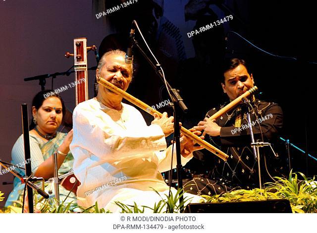 South Asian Indian Padma bhushan Hari prasad Chaurasia playing flute with his co-artist ; Mumbai Bombay ; Maharashtra ; India NO MR