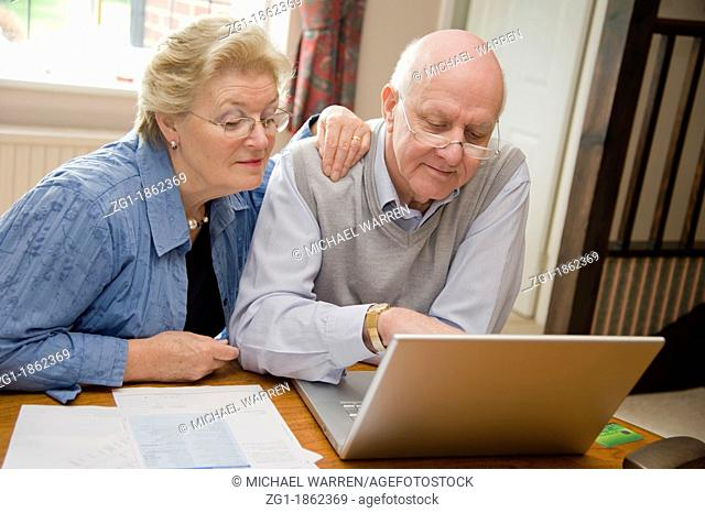 Mature couple confidently paying their bills together online