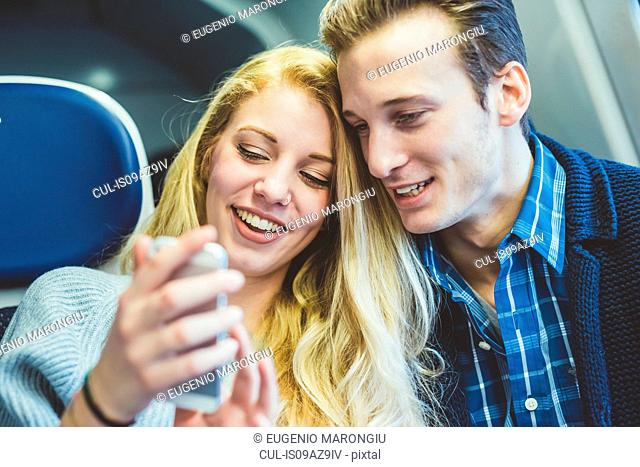 Young couple reading smartphone texts in train carriage