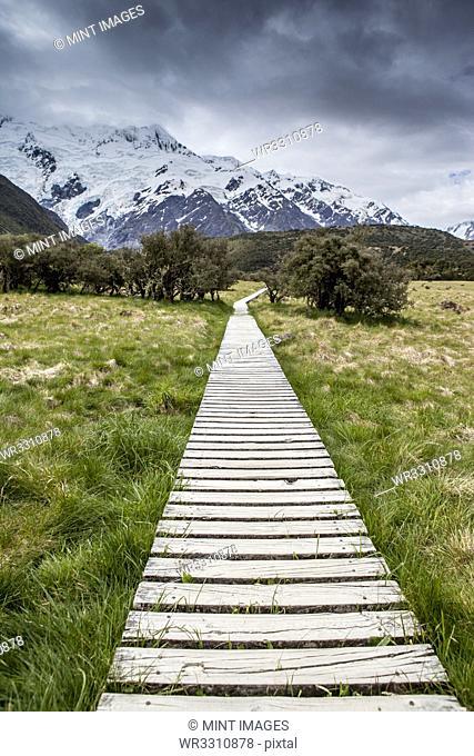 Wooden boardwalk toward mountain range