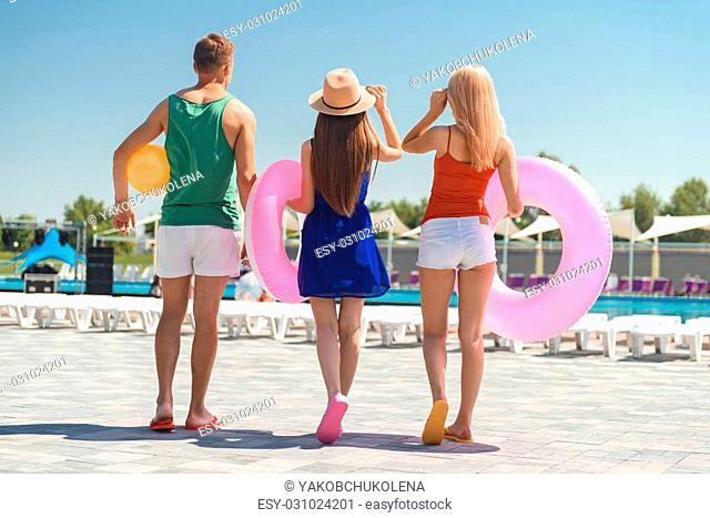 Young friends are going to swimming pool. They are carrying ball and rubber ring. Focus on their back