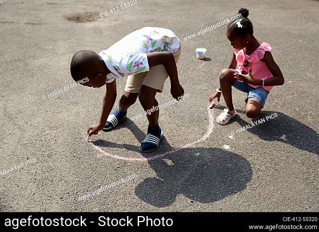 Brother and sister playing with sidewalk chalk on sunny pavement