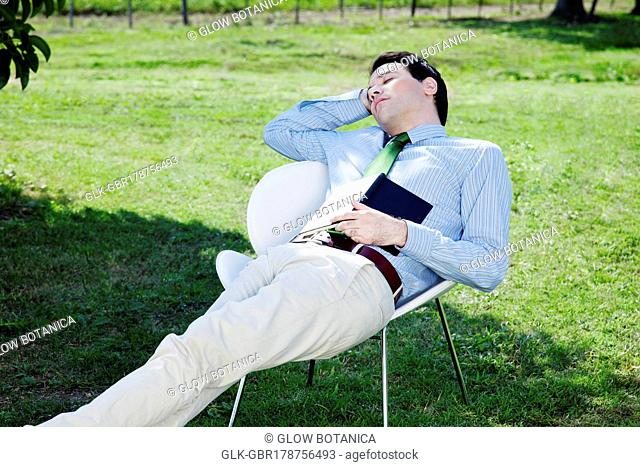 Businessman resting on a chair with a book in a field