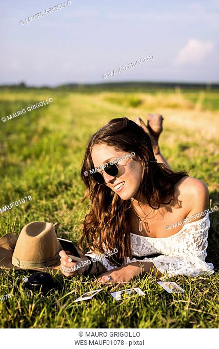 Happy woman lying in a field looking at instant photos