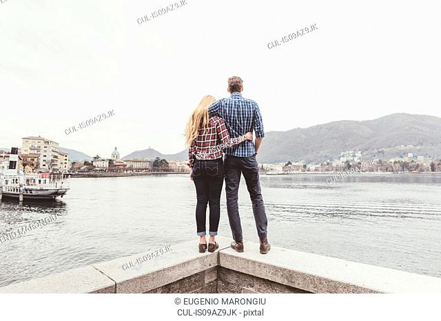 Rear view of young couple standing on harbour wall looking out, Lake Como, Italy