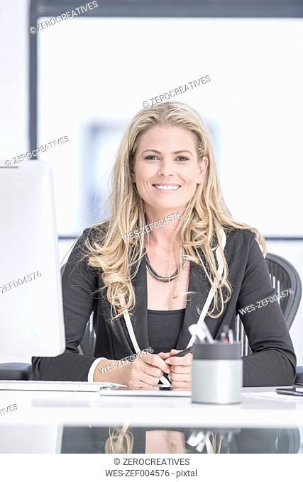 Confident businesswoman sitting at desk