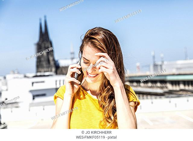 Germany, Cologne, smiling woman on the phone