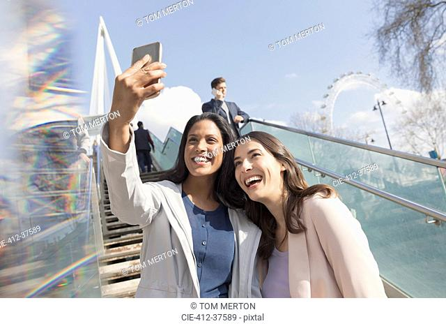 Enthusiastic, smiling women friends taking selfie with camera phone on sunny, urban stairs, London, UK