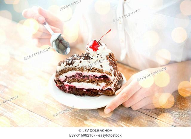 food, junk-food, culinary, baking and holidays concept - close up of woman eating chocolate cherry cake with spoon and sitting at wooden table over holidays...