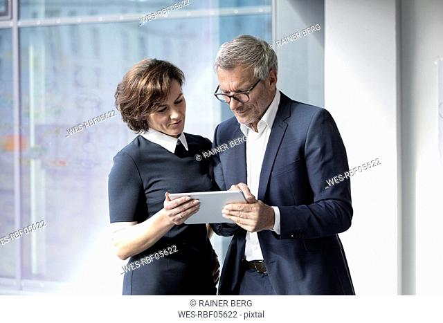 Businessman and businesswoman sharing tablet at the window