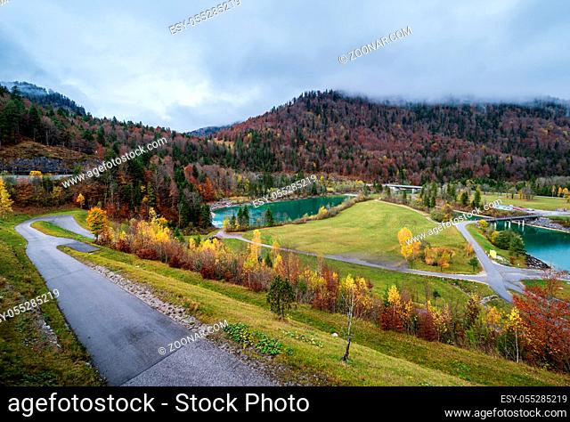 Alpine Isar river and Isarbrucke bridge view from Sylvenstein Stausee damm , Bavaria, Germany. Autumn overcast, foggy and drizzle day