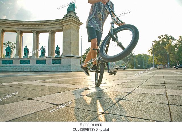 BMX cyclist doing wheelie, Heroes' Square (Hosök Tere), Budapest, Hungary