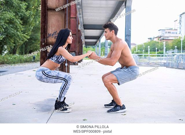 Young man and woman doing counterbalanced squat