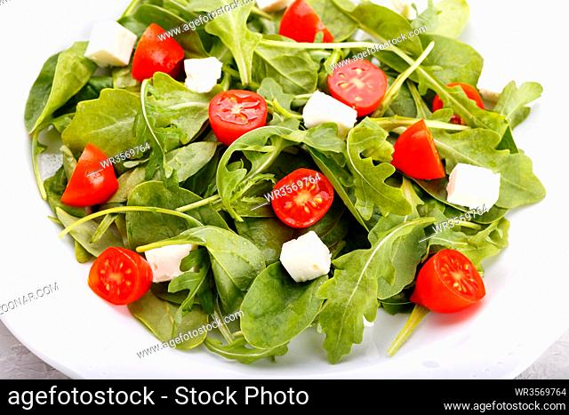 Salad with feta tomatoes lettuce on white plate close up