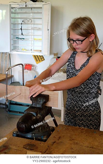6th Grade Girl Using Coping Saw With Vice in Technology Class, Wellsville, New York, USA