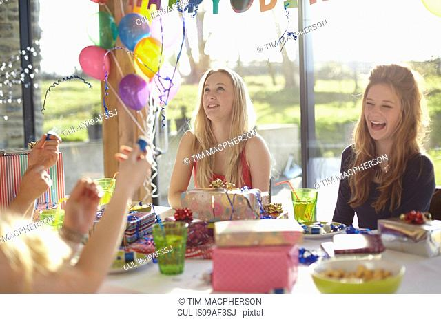 Four teenage girls celebrating with bubbles at birthday party