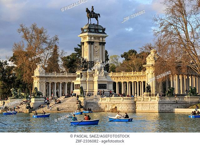 People relax by the pond in the Retiro park in Madrid