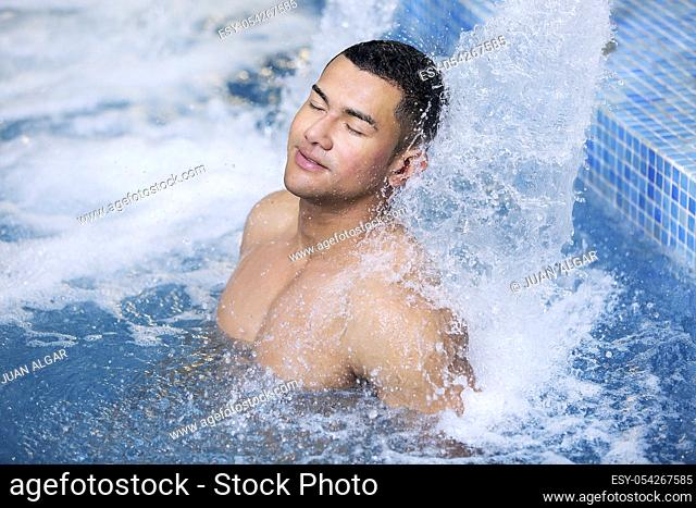 Smiling man with eyes closed relaxing under stream of hydrotherapy shower. Horizontal indoors shot