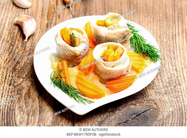 Pickled herring rolls with vegetables on wooden table